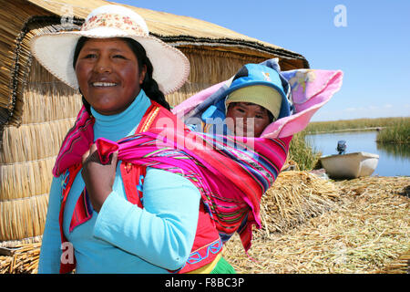 Uros Indian Woman And Her Baby Being Carried In Traditional Papoose - Stockfoto