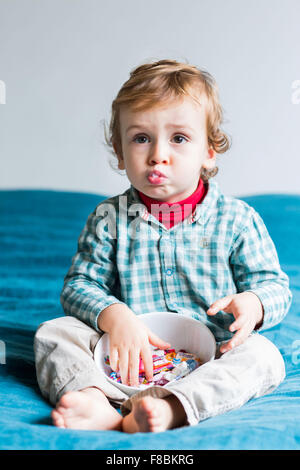 2 year-old boy eating sugary sweets. - Stock Photo