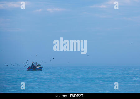 Fisher ship, blue Pacific Ocean and many birds flying over, Peru - Stock Photo