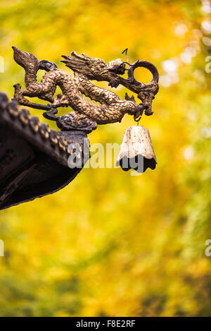 Dragon sculpture with a bell on a roof of a chinese temple with yellow leaves from autumn trees in the background - Stock Photo