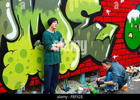 Boys painting graffiti on the wall in Lisbon.Along with London, Berlin, New York and other - Stockfoto