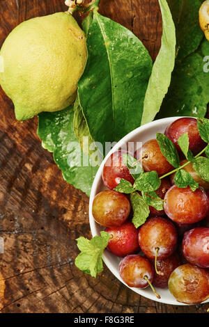 Red plums in bowl on wood surrounded by lemon and green - Stock Photo