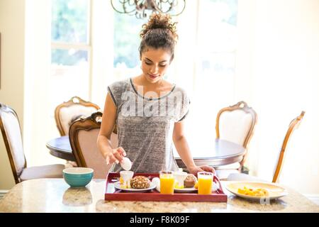 Young woman at home preparing breakfast tray, looking down holding egg - Stock Photo