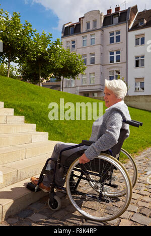Elderly woman in wheelchair looking at stairs - Stock Photo