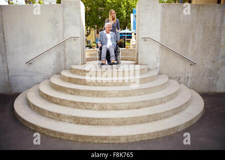 Elderly woman in wheelchair looking at inaccessible staircase - Stock Photo
