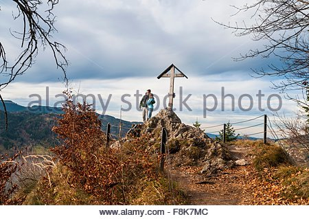 Couple by wood structure arms around each other looking at view, Schliersee, Bavaria - Stock Photo