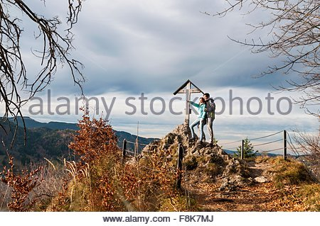 Couple by wood structure arms around each other looking at view pointing, Schliersee, Bavaria - Stock Photo