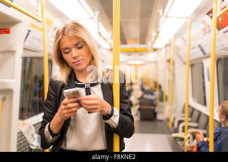 Businesswoman texting on tube, London Underground, UK - Stock Photo