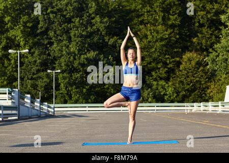 Young woman practicing yoga tree pose in urban parking lot - Stock Photo