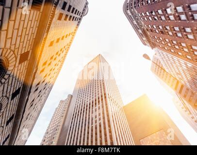 Low angle view of sunlit office skyscrapers, Manhattan financial district, New York, USA - Stock Photo
