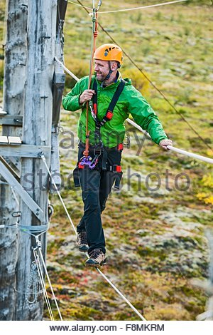 Man balancing at high rope access course, Iceland - Stock Photo