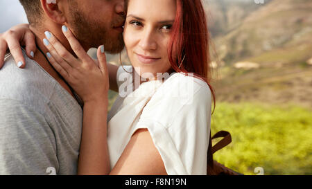 Close up shot of attractive young woman hugging her boyfriend outdoors. Romantic young couple on holiday. - Stock Photo