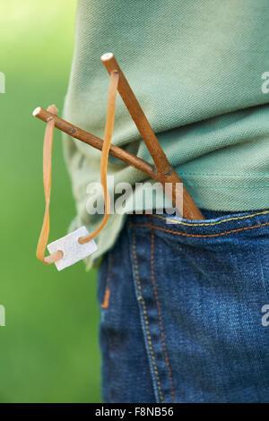 Close Up Of Slingshot In Boy's Trouser Pocket - Stock Photo