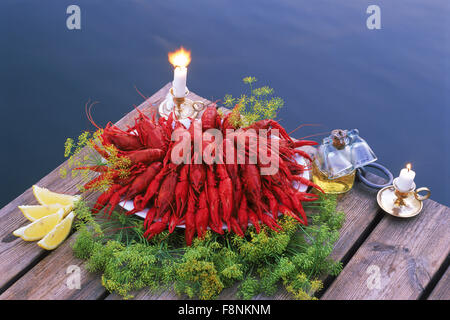 Bowl of crayfish on lakeside pier with candles and aquavit in Sweden - Stock Photo
