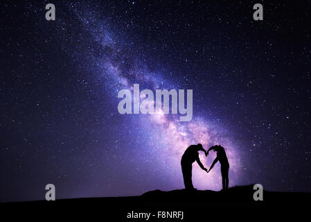 Man and woman holding hands in heart shape on the background of the Milky Way - Stock Photo
