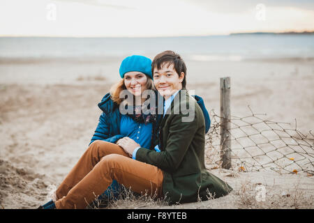 young couple sitting and posing on the beach in autumn - Stockfoto