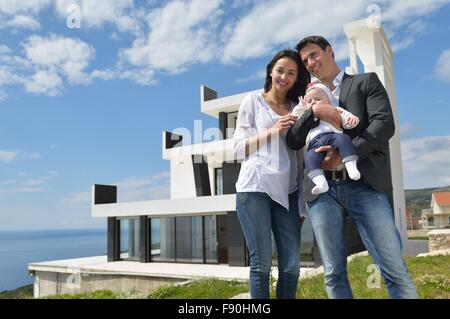 happy young family couple with beautiful new born baby have fun at home - Stock Photo