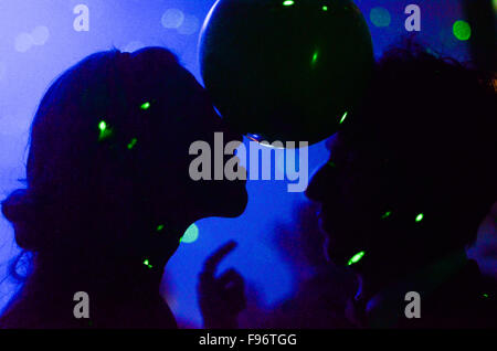 Silhouette Of Couple Dancing With Ball Held With Foreheads - Stock Photo