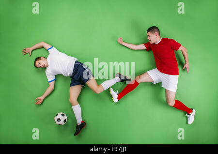 Two enthusiastic football players fighting for a ball. Studio shot on a green backgroud. - Stock Photo