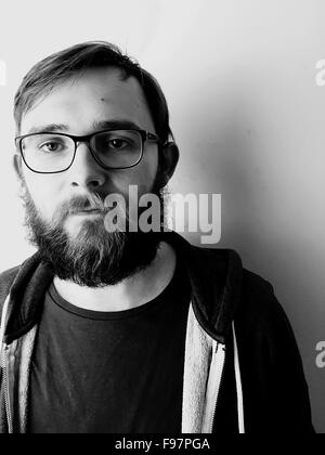 Portrait Of Man With Eyeglasses Standing Against Wall At Home - Stock Photo