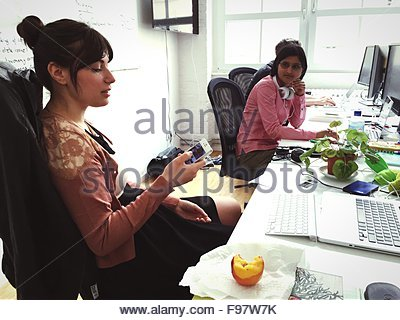Beautiful Businesswoman Using Phone While Female Colleague Looking At Her In Office - Stock Photo