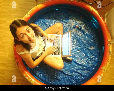 Portrait Of Woman Using Laptop In Wading Pool - Stock Photo