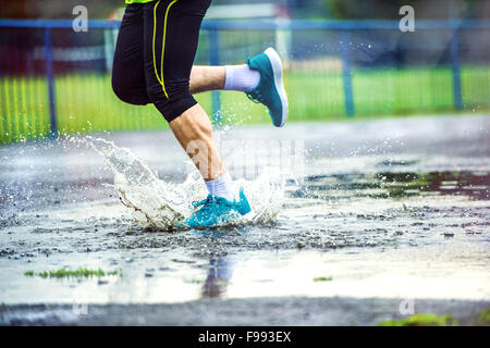 Young man running on asphalt sports field in rainy weather. Details of legs and sports shoes splashing in puddles. - Stock Photo