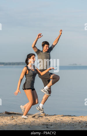Beach running couple jogging outside. Runners training outdoors working out at seaside in the background. Fit multiracial - Stock Photo