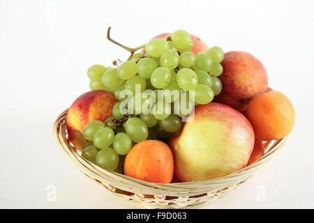 Fruit basket with apple peach grape and apricot on white background - Stock Photo