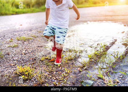 Little boy playing outside in a puddle - Stock Photo