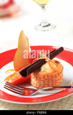 Cream filled puff pastry shell garnished with fresh fruit - Stock Photo