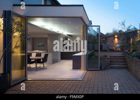 Kitchen and dining areas seen through open bi-fold doors from the patio and garden at dusk. A modern family home. - Stock Photo