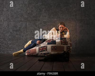 Girl Listening Music on Beanbag at home - Stock Photo