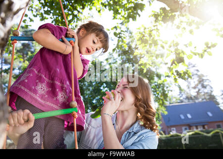 Mother eating an apple with daughter on rope ladder in garden - Stock Photo