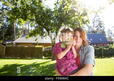Mother holding daughter with apple in garden - Stock Photo