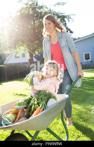 Mother pushing daughter with vegetables in wheelbarrow in garden - Stock Photo