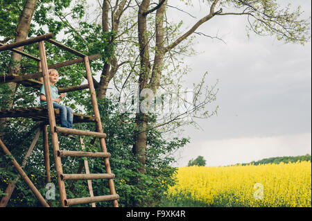 Germany, Saxony, boy sitting on raised hide looking out - Stock Photo