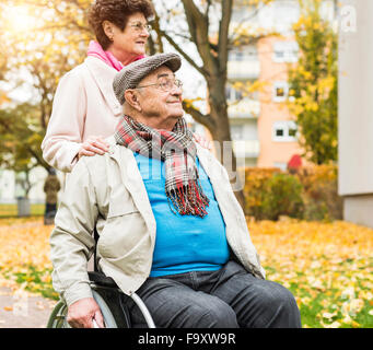 Senior woman with husband in wheelchair outdoors - Stock Photo