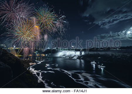 A moonlit fireworks celebration at Niagara Falls Ontario Canada at night showing the falls the motion in the river - Stock Photo
