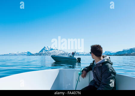 Young man sitting in boat looking at snowcapped mountains - Stockfoto