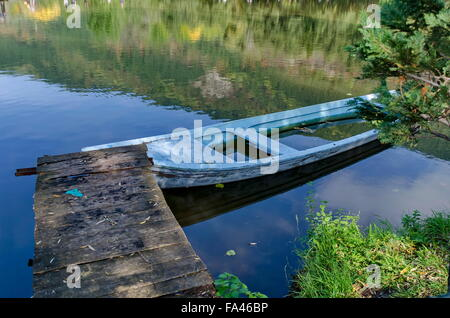 Old abandoned boat by lake - Stock Photo