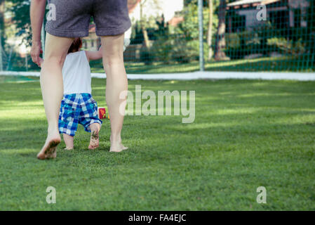 Mother helping her baby boy to take first steps, Munich, Bavaria, Germany - Stock Photo