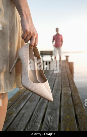 Mature man waiting for her wife on pier at lake, Bavaria, Germany - Stock Photo