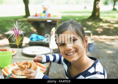Portrait of a girl eating food at picnic, Munich, Bavaria, Germany - Stock Photo