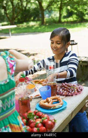 Girl eating food and smiling at picnic, Munich, Bavaria, Germany - Stock Photo