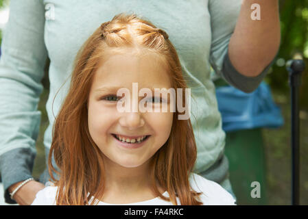 Portrait of a girl smiling with her mother in picnic, Munich, Bavaria, Germany - Stock Photo
