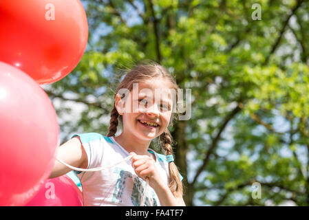 Portrait of a smiling girl holding red balloons, Munich, Bavaria, Germany - Stock Photo