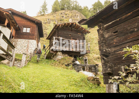 Rear view of two mature hikers passing by cottages, Austrian alps, Carinthia, Austria - Stock Photo