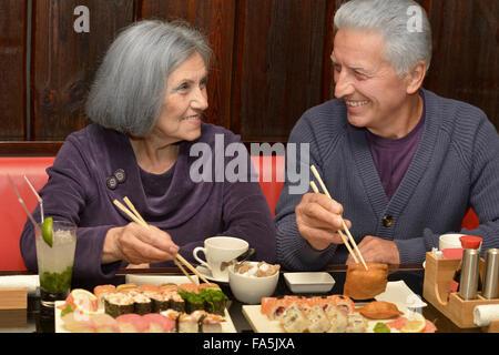 Elderly couple eating sushi - Stock Photo