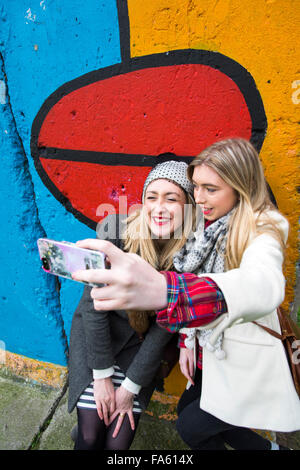 Girls take a selfie at part of Berlin Wall Germany - Stockfoto